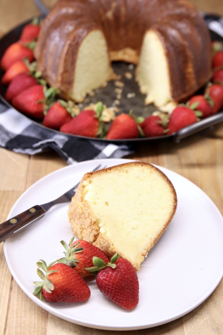 Amaretto Pound Cake - slice on a plate with fresh strawberries and cake on a platter in background