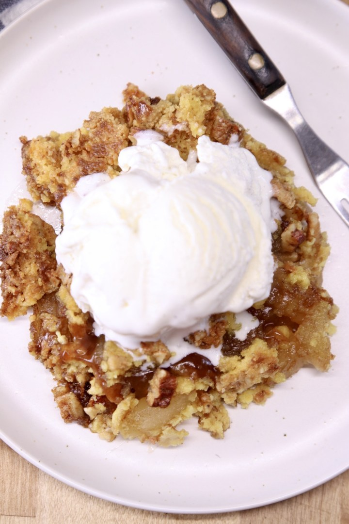 apple dump cake with vanilla ice cream on a plate with a fork