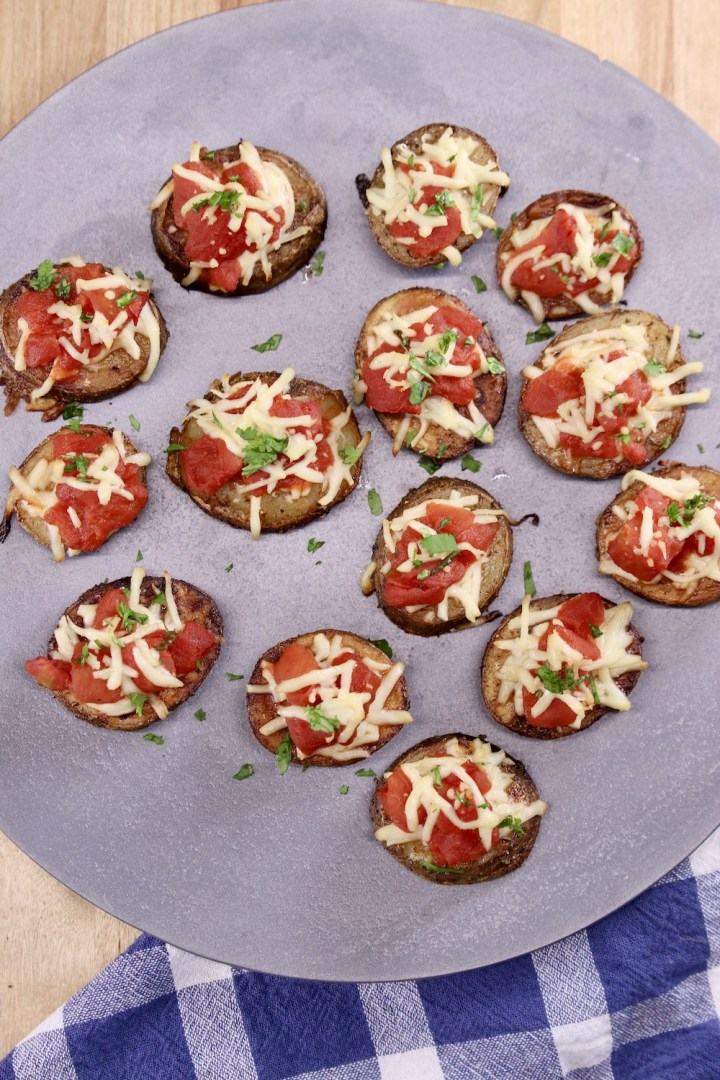 platter of potato slices topped with tomatoes and mozzarella