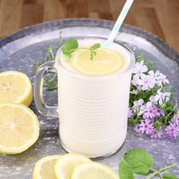 frosted pineapple lemonade in a glass with straw and slice of lemon. Sitting on a tray with lemon slices and small flowers