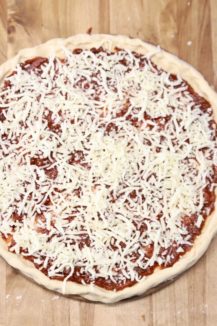 pizza topped with shredded cheese