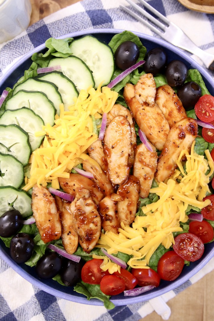 close up of chicken salad with bbq chicken, tomatoes, cheese, cucumbers, olives
