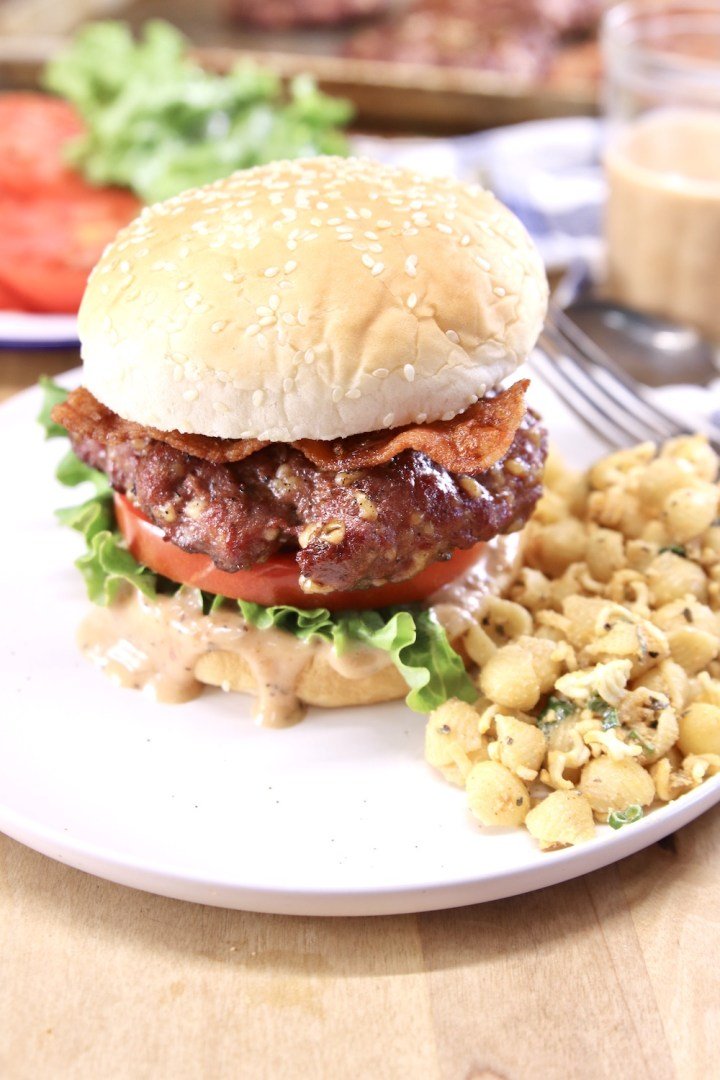Burger on a plate with pasta salad