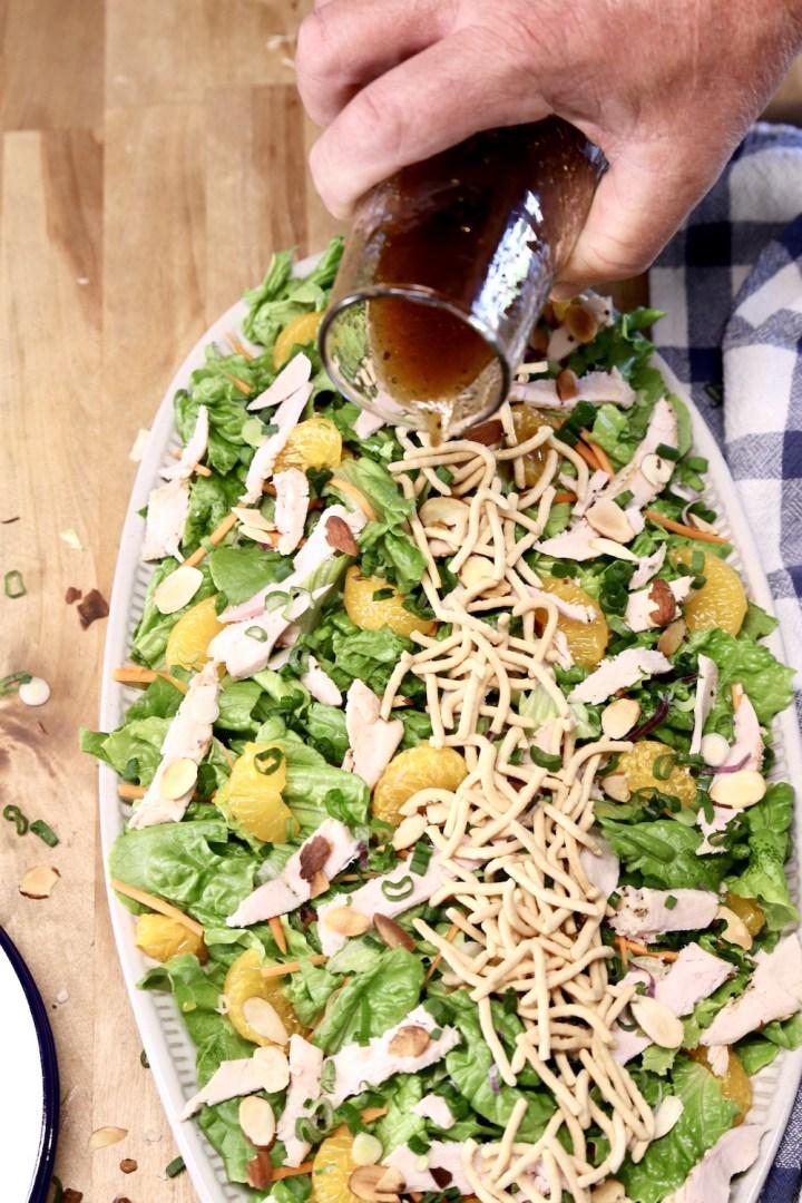 pouring dressing over platter of salad