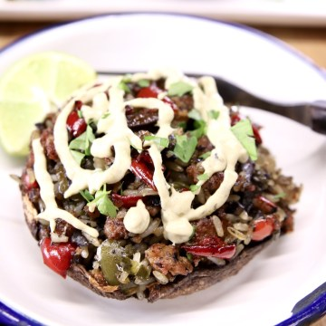 stuffed portobello mushroom with sausage, peppers, rice and cream sauce drizzle