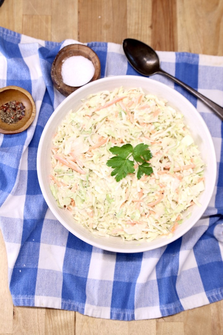 coleslaw in a bowl on a blue napkin, spoon, small bowls of salt & pepper all on a blue check napkin