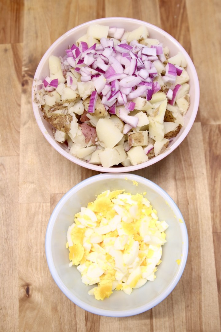 bowl with diced potatoes and red onions, smaller bowl with diced hard boiled eggs