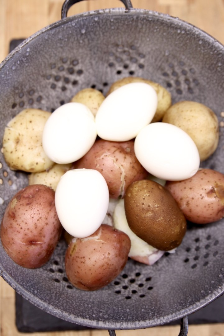 colander with boiled potatoes and hard boiled eggs