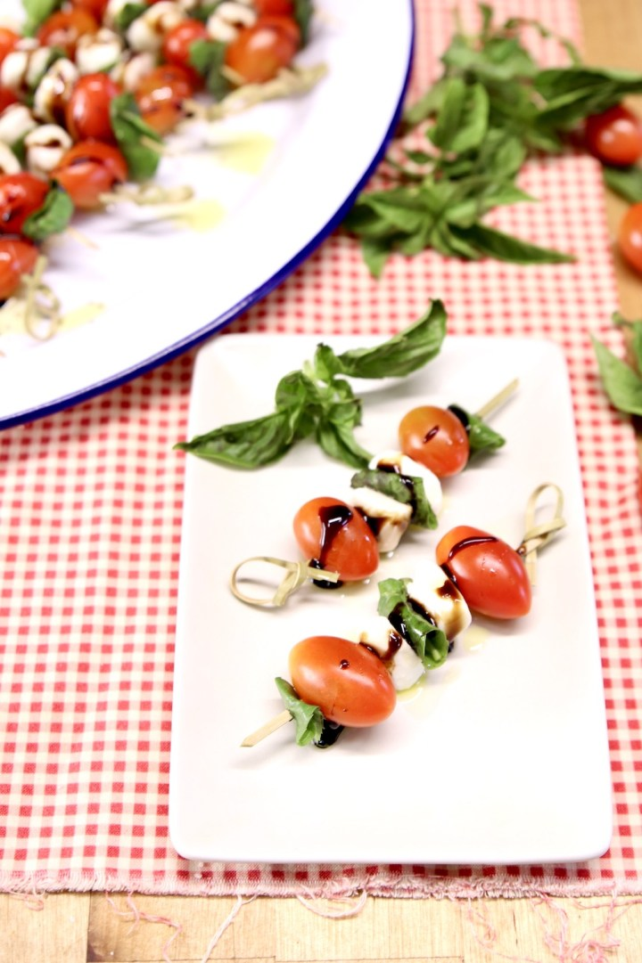 appetizer plate with 2 caprese salad skewers