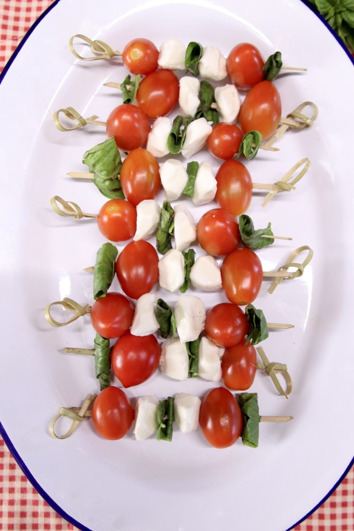 tomato, mozzarella balls and basil on bamboo skewers on a platter