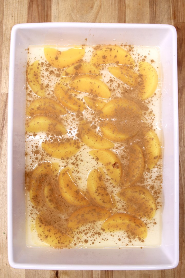 cinnamon sprinkled over sliced peaches in a cake pan