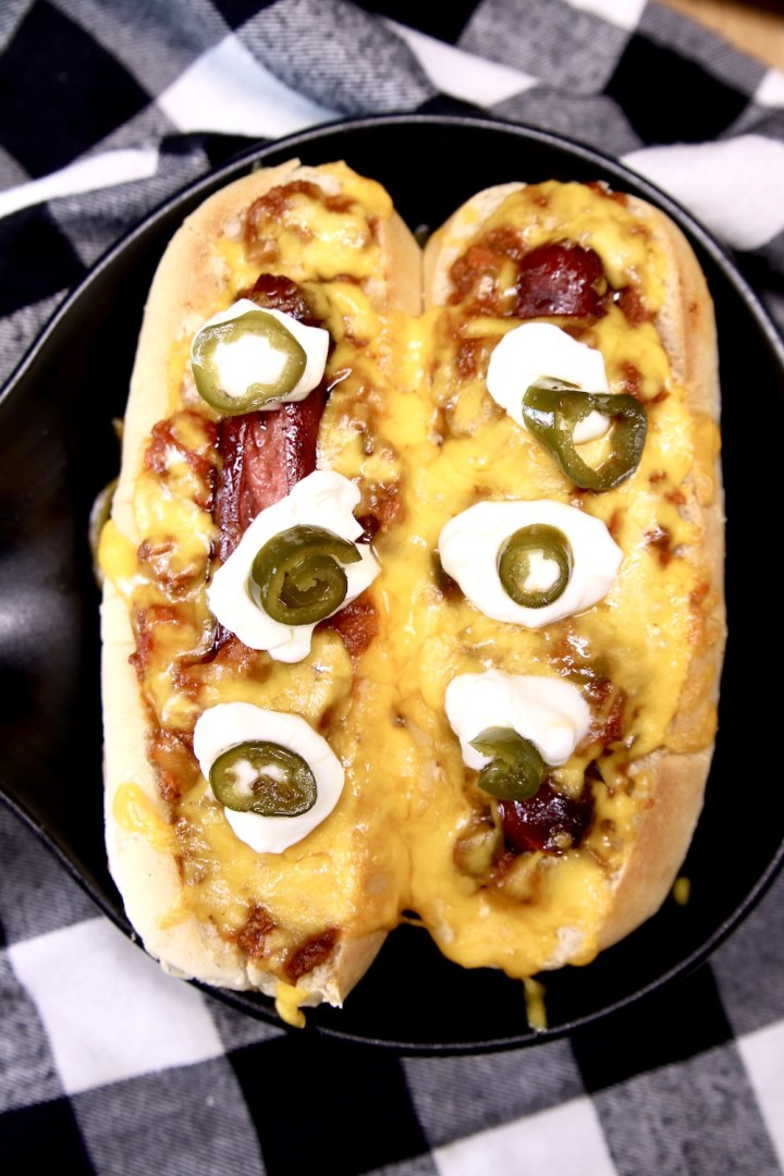 2 chili dogs with sour cream dollops and jalapenos