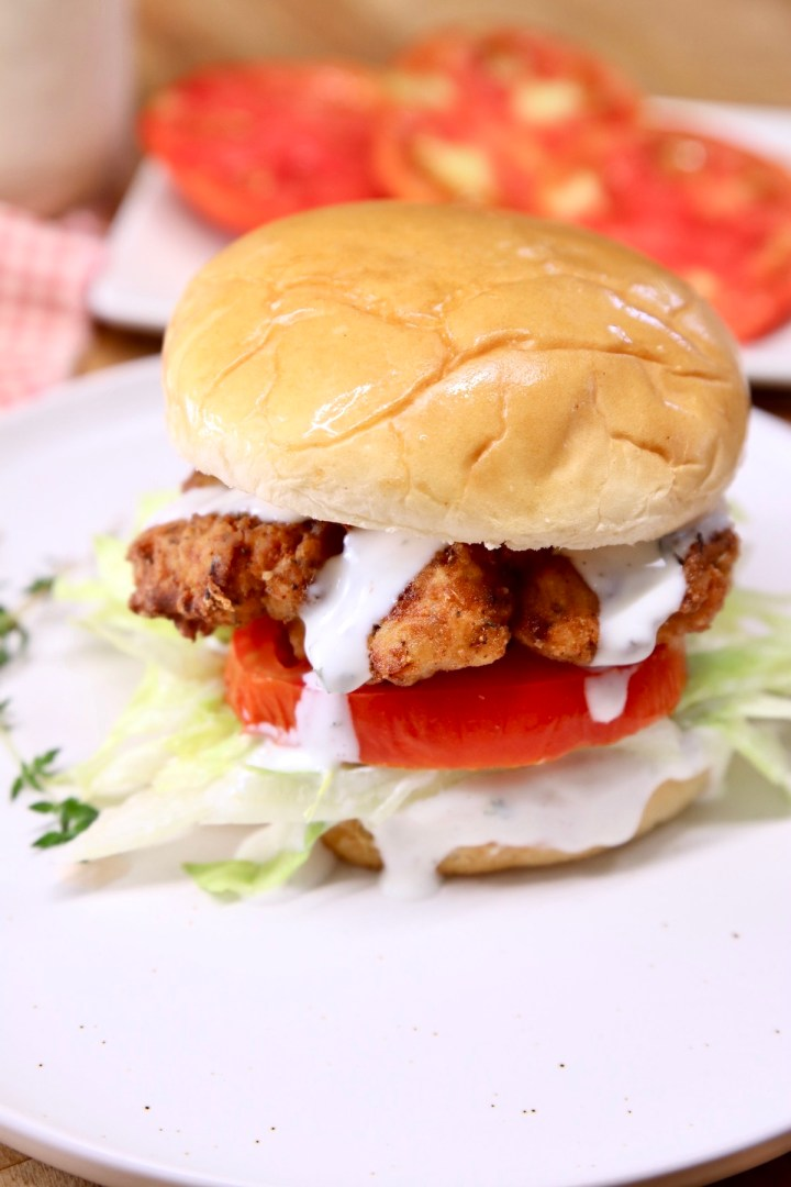 fried chicken sandwich with lettuce, tomato and ranch dressing drizzle