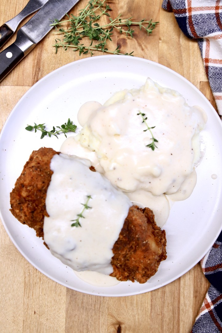 plate with fried pork chop and mashed potatoes, topped with white gravy