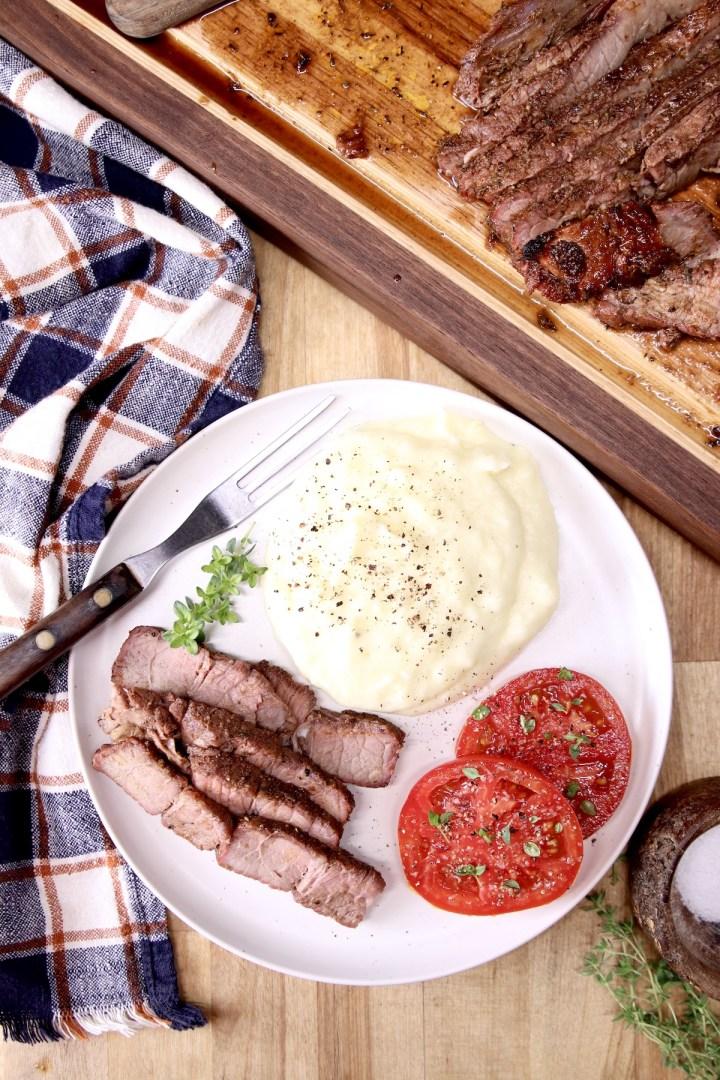 Plate of sliced roast, mashed potatoes, sliced tommatoes