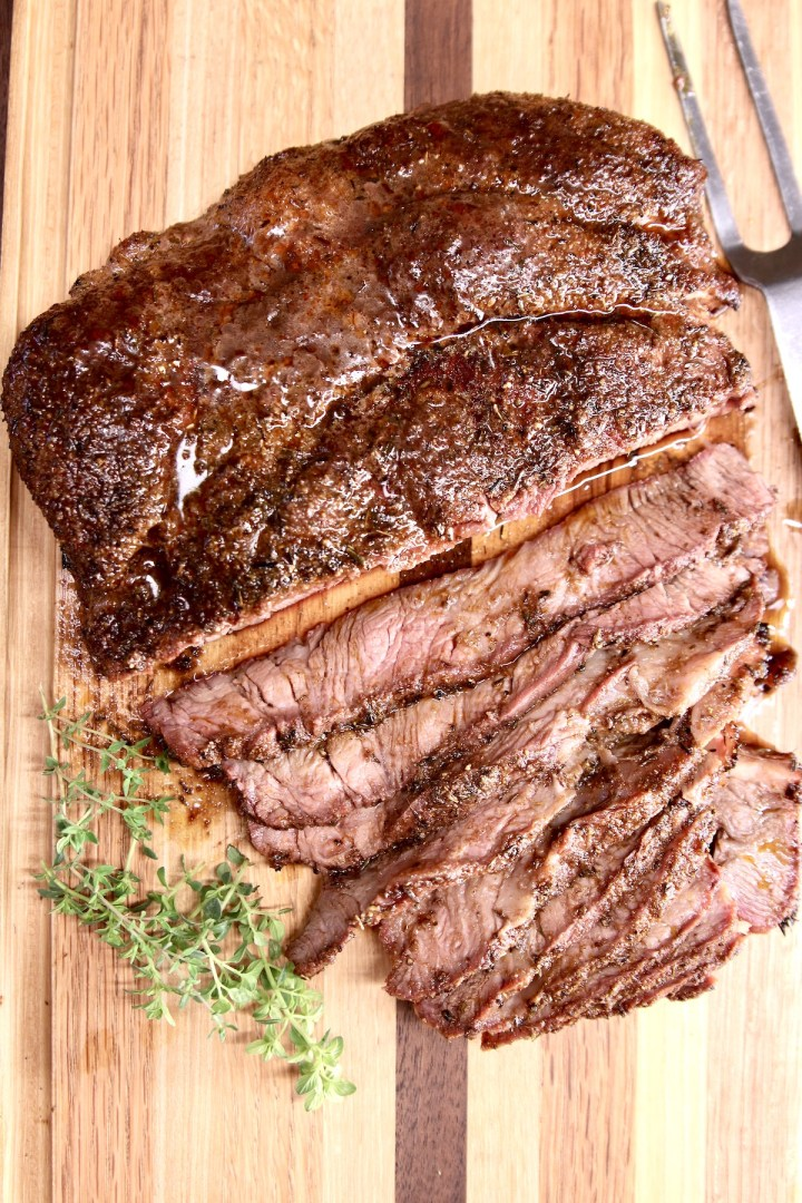 chuck roast on a cutting board with fresh thyme, partially sliced