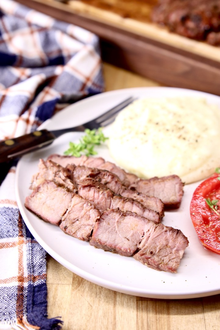 Grilled roast beef slices on a plate with mashed potatoes