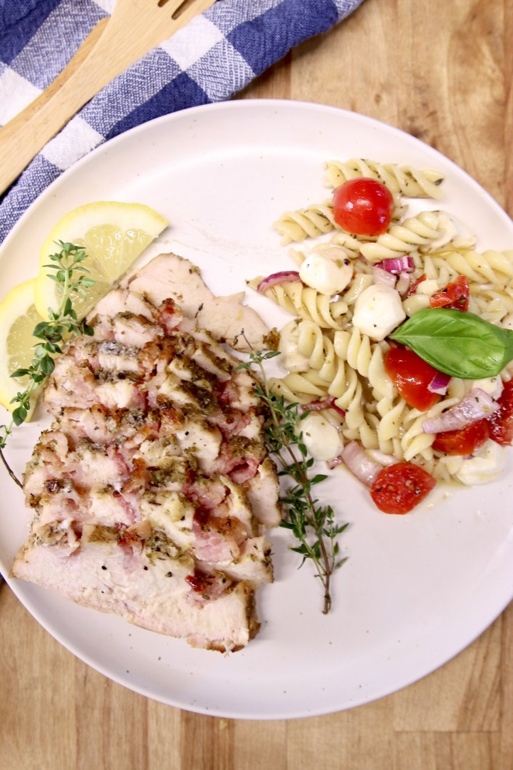plate of sliced chicken and pasta salad with tomatoes, mozzarella and basil