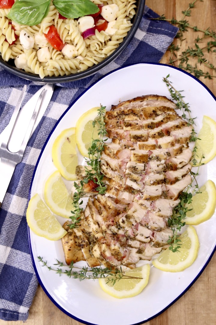 Chicken sliced on an oval platter, pasta salad in back ground