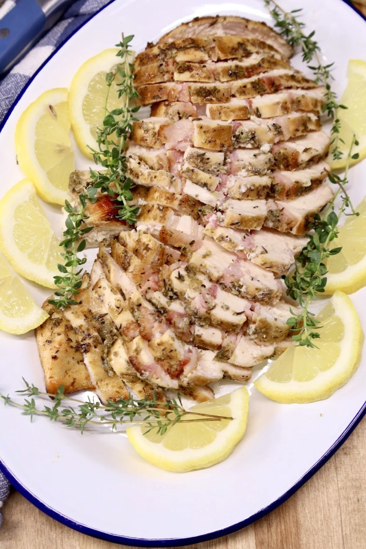 Platter of sliced chicken with lemon and thyme garnish