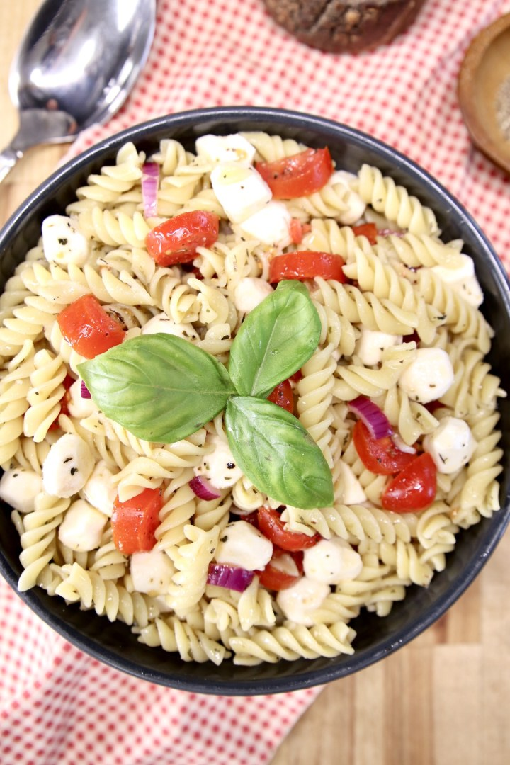 overhead view of pasta salad in a black bowl. Tomatoes, mozzarella and basil garnish