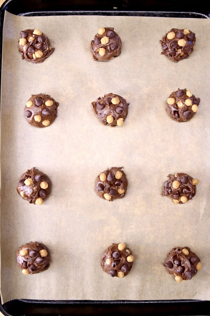cookie dough balls with chocolate chips and caramel bits on a parchment lined baking sheet