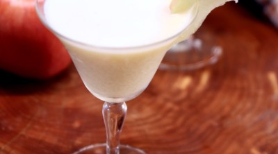 creamy caramel apple martini in a coupe glass with apple slice garnish