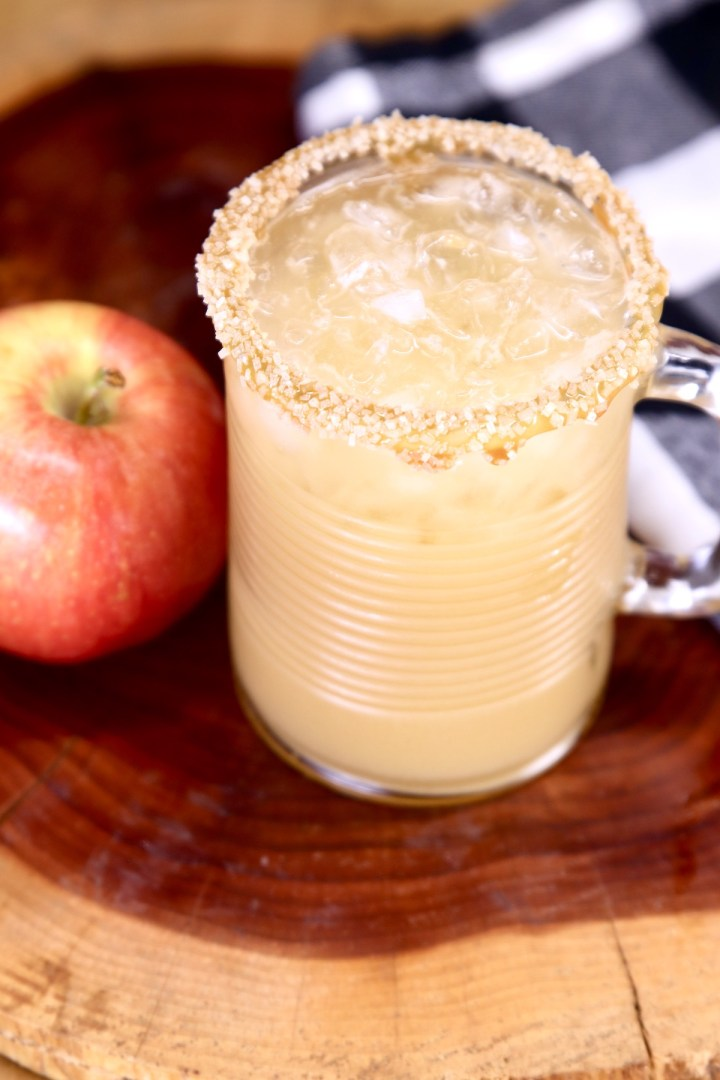 glass of caramel apple cocktail with apple to the side