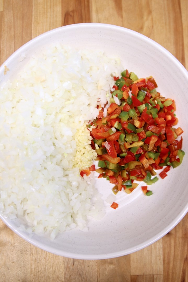 bowl of diced onions, minced garlic, diced red and green bell peppers