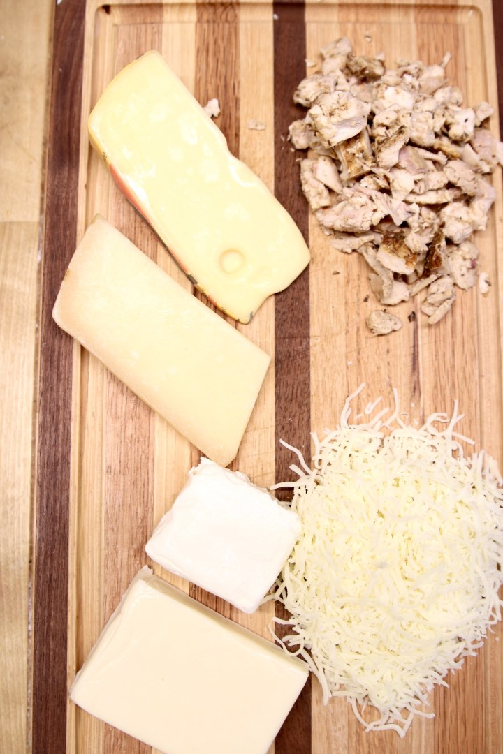 cutting board with 5 kinds of cheese, smoked chicken, diced