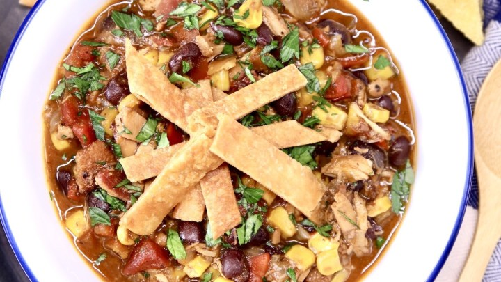 Chicken tortilla soup in a bowl topped with crispy tortilla strips
