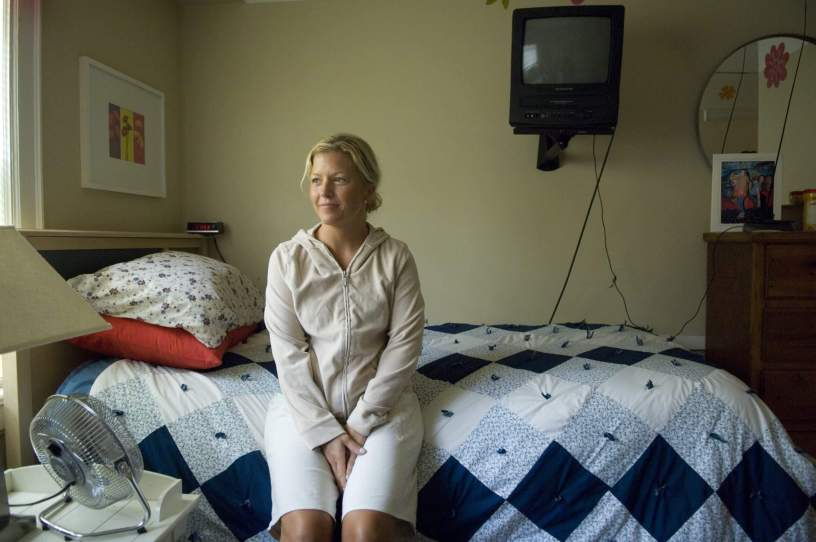 woman sits on a bed