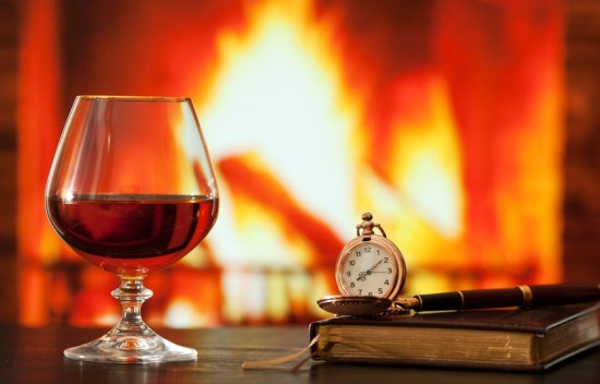 Brandy glass, diary and pocket watch on the table near the burning fireplace
