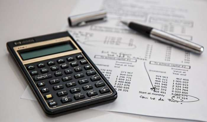 calculator and pen sitting on top of piece of paper of budgeting tips