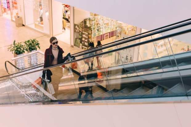 woman riding escalator in shopping mall thinking about budgeting tips