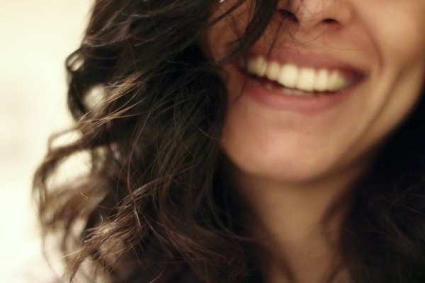 woman smiling at camera to boost your confidence