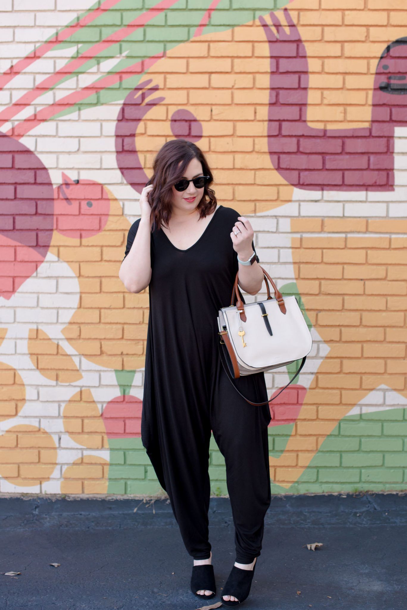 The Most Comfortable Jumpsuit for Spring // Miss Molly Moon | The Most Comfortable Jumpsuit Ever featured by top Atlanta fashion blogger, Miss Molly Moon: image of a woman wearing an Amazon black jumpsuit, Fossil bag, Ray Ban sunglasses and Target block heel mules