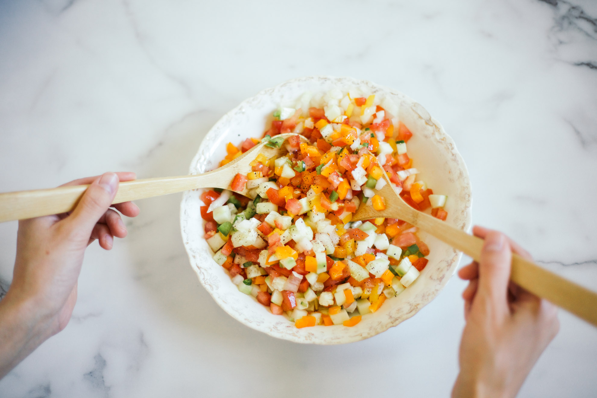 mixing fresh mediterranean salsa with wooden spoons