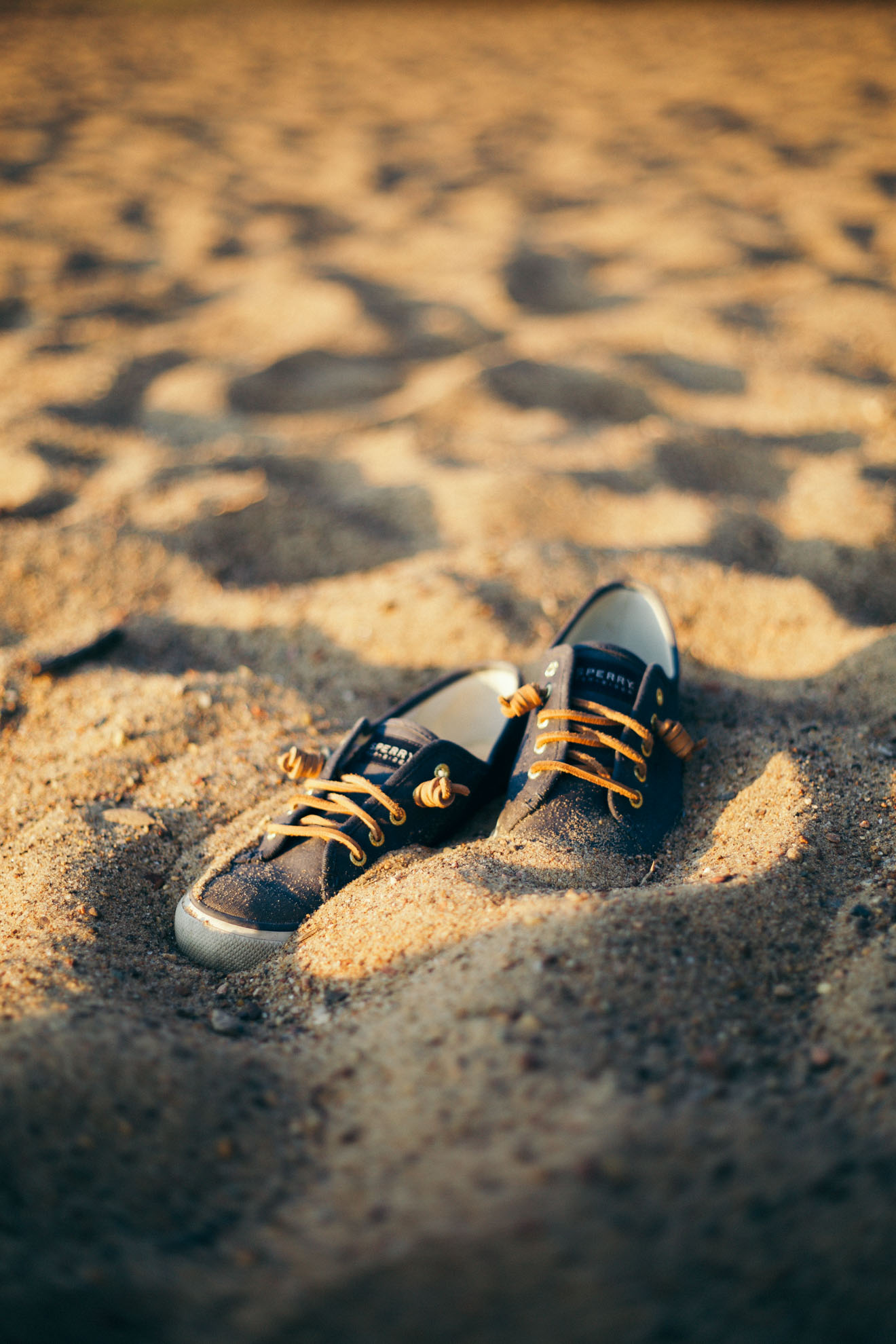 sperry sneakers in the sand on beach in wisconsin at sunset