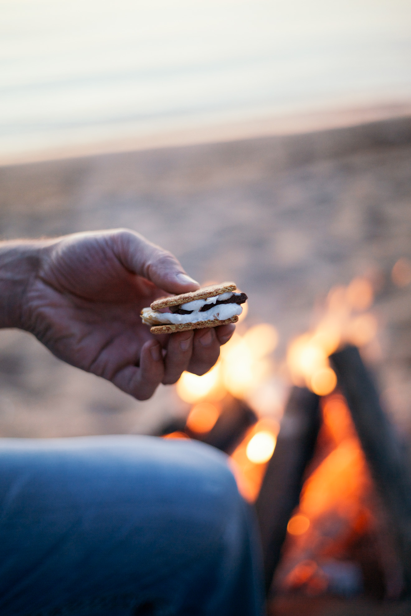 holding a smore by campfire on a beach in wisconsin