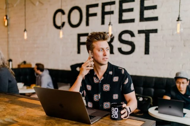 real estate selling tips- man on computer drinking coffee