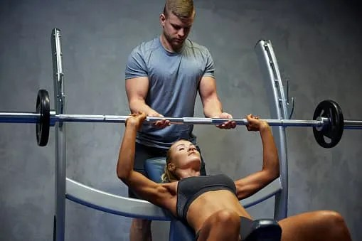 strength training program- workout with spotter on bench