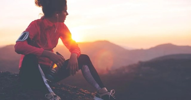 Health and fitness tips- female runner taking a break sitting atop mountain