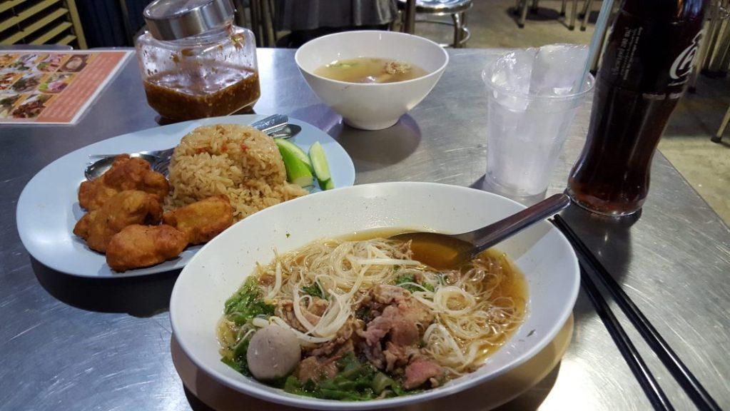 """So ein Sonnenuntergang macht hungrig. Nun wollte ich zum letzten Mal nochmal richtiges Thai-Food essen und nicht in so einem Touristenlokal direkt in Hotelnähe meinen letzten Abend verbringen. Also wanderte ich ein wenig durch die Gegend und fand eine typisches Open Air Restaurant mit offener Garküche – """"Too fast Chicken Rice"""". Perfekt."""