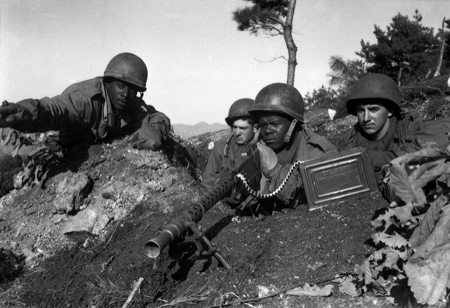Fighting with the 2nd Inf. Div. north of the Chongchon River, Sfc. Major Cleveland, weapons squad leader, points out communist-led North Korean position to his machine gun crew. November 20, 1950.