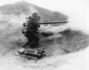 Powder smoke and dust billow as a recoilless rifle team of Co. D, 7th infantry Regiment, 3rd U.S. Infantry Division, fire their weapon at Chinese Communist positition on Hill 200 near Qnmong-Myon, Korea. 9 November 1951 (Photo: U.S. Army)