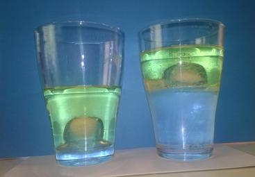 Links das Glas mit Öl und einem Eiswürfel, rechts das Glas mit Wasser, Öl und einem Eiswürfel.
