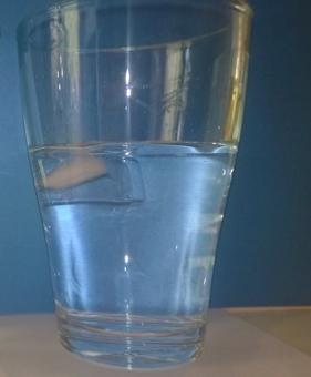 Ein Eiswürfel schwimmt in einem Glas mit Wasser.