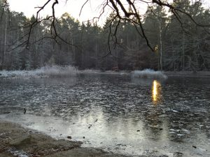 Die Sonne geht über einem zugefrorenen See unter.