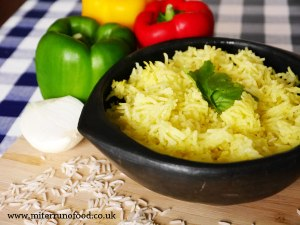 yellow rice served in a bowl with peppers next to it